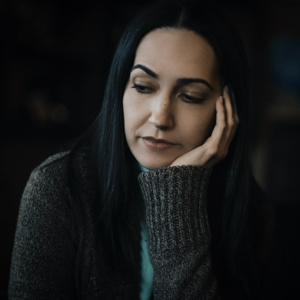 A woman wearing a gray sweater and looking sad. | Photo: Pexels