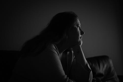 Grayscale Photo of Woman Sitting on Sofa With Her Head On Her Hand Looking Away