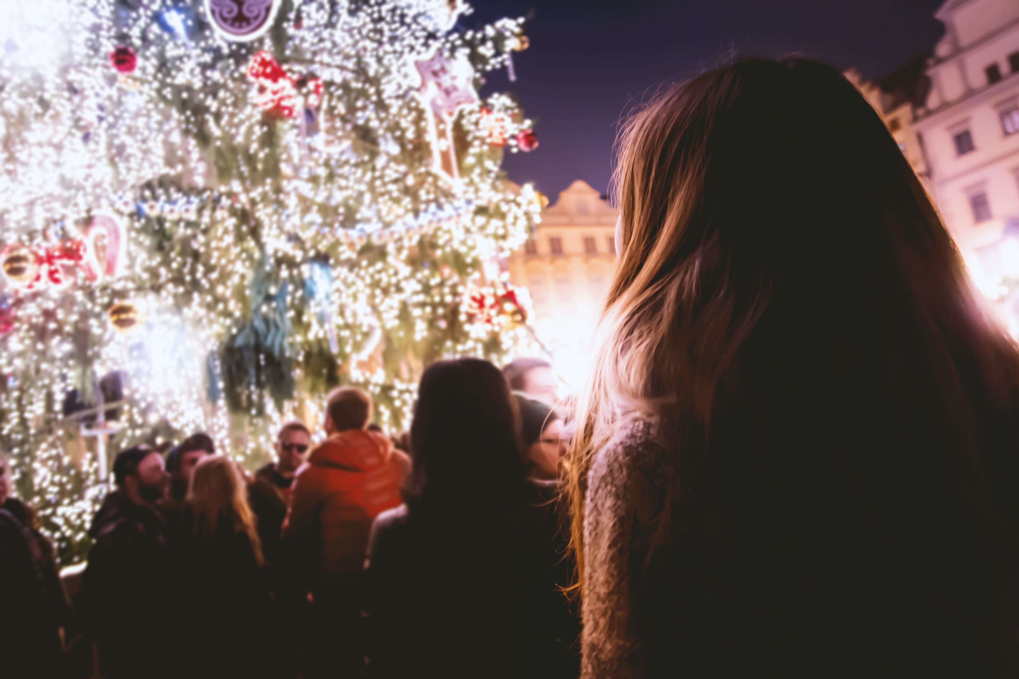 People Standing Facing Christmas Tree With Lights during Night Time