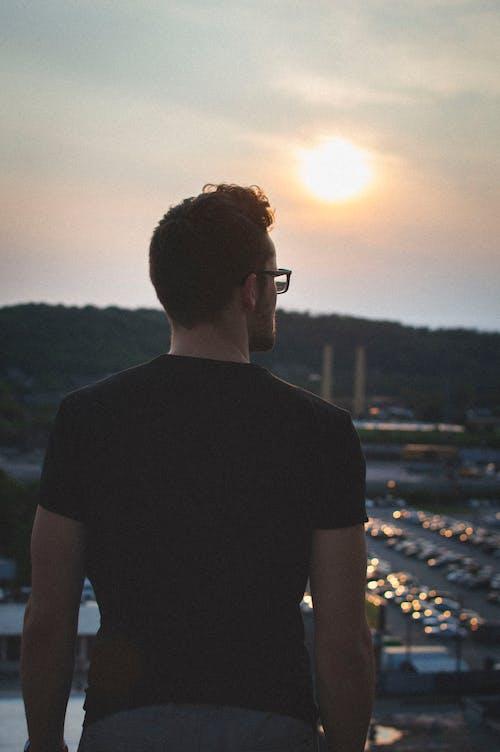 20-25 yaşında erkek, akşam Güneşi, altın rengi Güneş, Kent içeren Ücretsiz stok fotoğraf