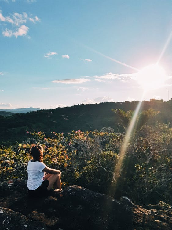 Photo of Woman Sitting on Cliff