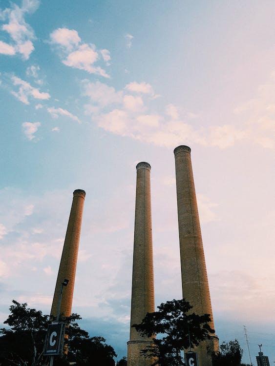 Three Beige Towers Under White Clouds