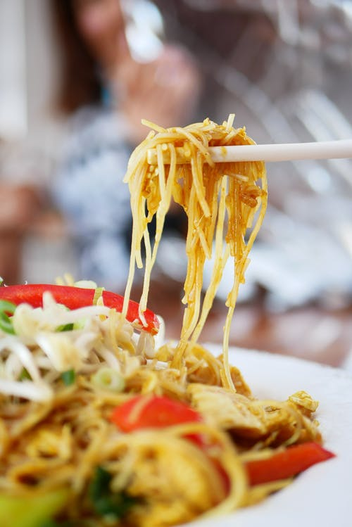 Person Picking Cooked Noodles with Chopsticks