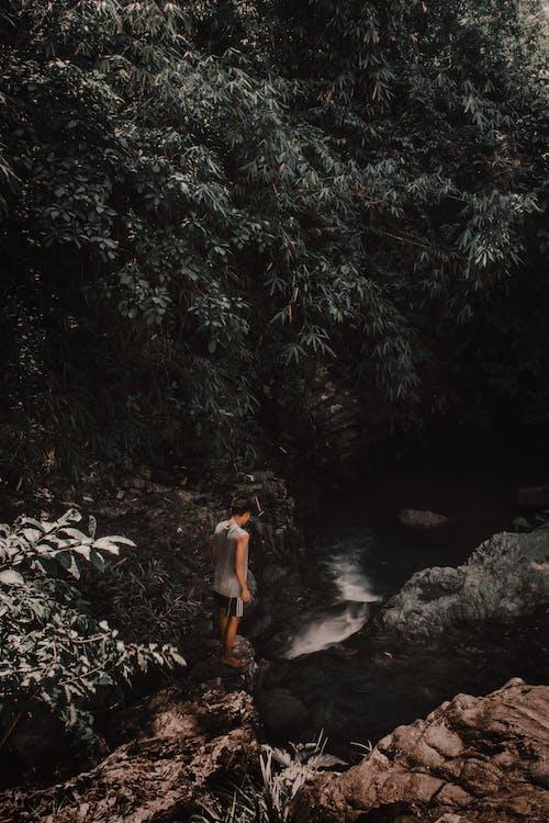 Photo of Man Standing on Rocks Near River