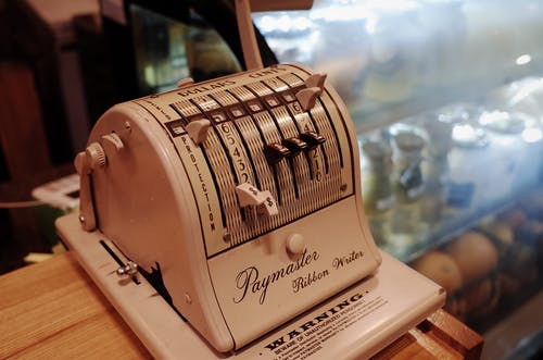 White Paymaster Ribbon Writer Adding Machine Placed on Tabletop