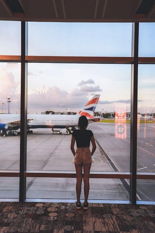 Photo of Woman Standing Near Glass Wall