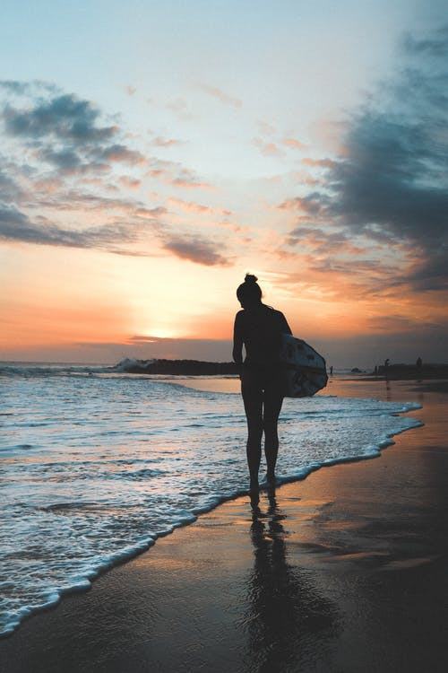 Silhouette Photography of Woman Standing by the Seashore Carrying Surfboard