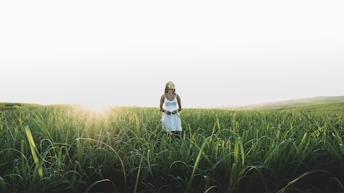 Woman Standing On Grass Field