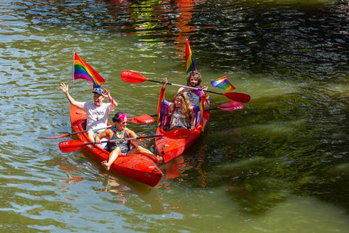 Four People Riding Kayaks