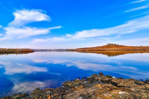 Бесплатное стоковое фото с голубая вода, голубое небо, красные скалы, летающие облака