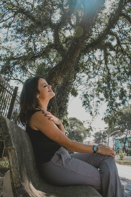 Photo of Woman Sitting on Bench Near Tree