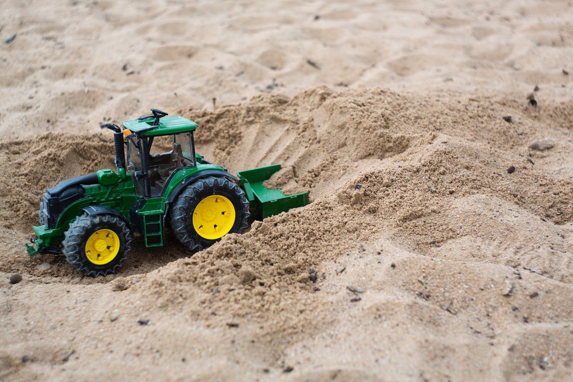 Green and Yellow Toy Bulldozer on Sand