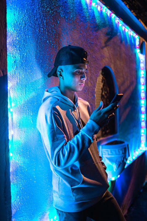 Side View Photo of Man Using Smartphone Leaning on Wall With Colorful Christmas Lights