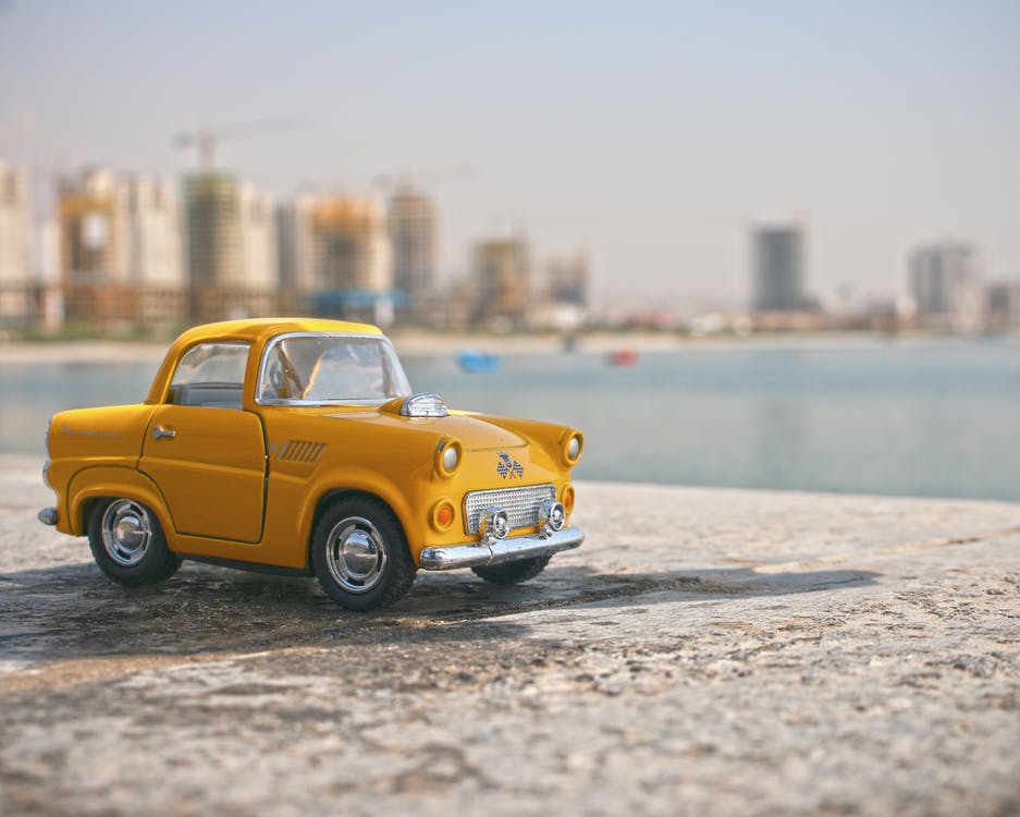 Selective Focus Photography of Yellow Car Toy
