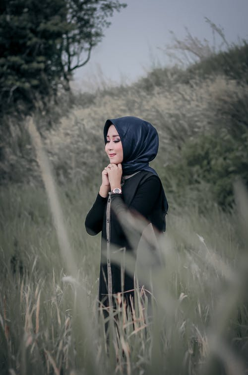 Photo of Smiling Woman in Black Hijab Standing in Grass Field with Her Eyes Closed