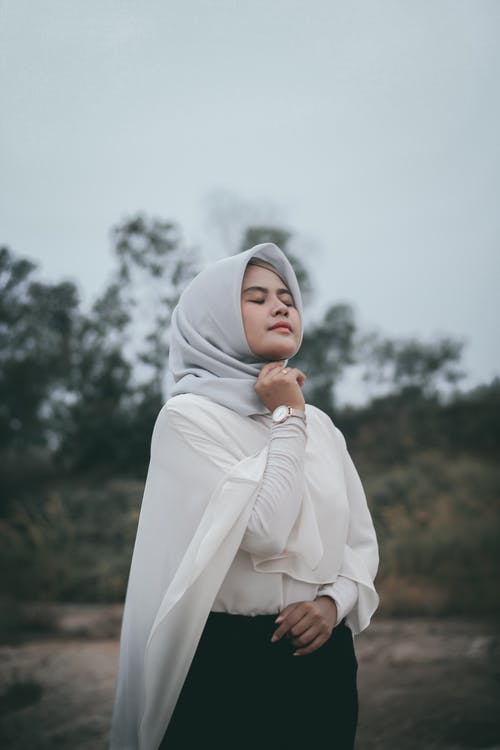 Photo of Woman in White Long-sleeved Shirt and Grey Hijab Posing With Her Eyes Closed