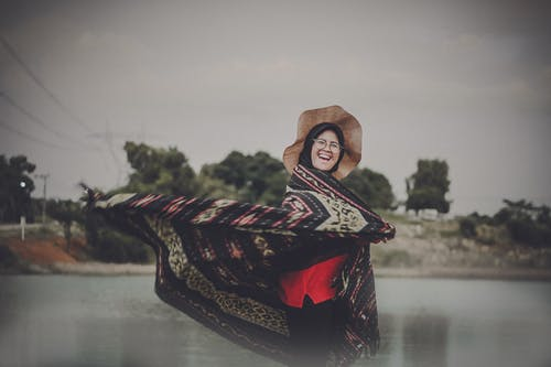 Photo of Laughing Woman in Hat and Hijab Standing by Body of Water While Flipping Her Shawl