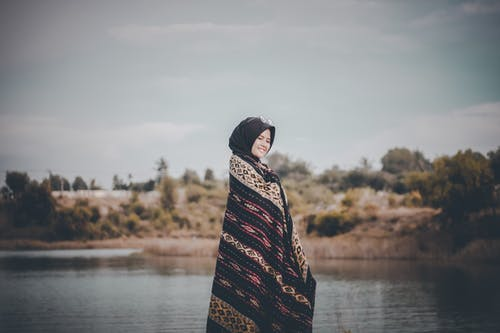 Side View  Photo of Smiling Woman in Hijab Standing by Body of Water While Covering Herself with a Shawl