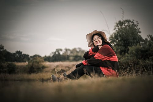 Woman Sitting on Grass Wearing Red-and-black Long-sleeved Shirt and Black Pants