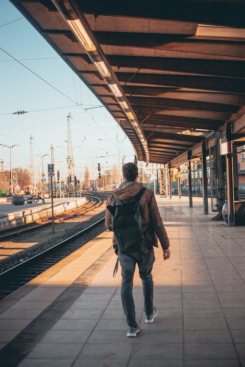 Back View Photo Man in Brown Hoodie, Gray Pants and Backpack Walking Alone at Empty Train Station Platform