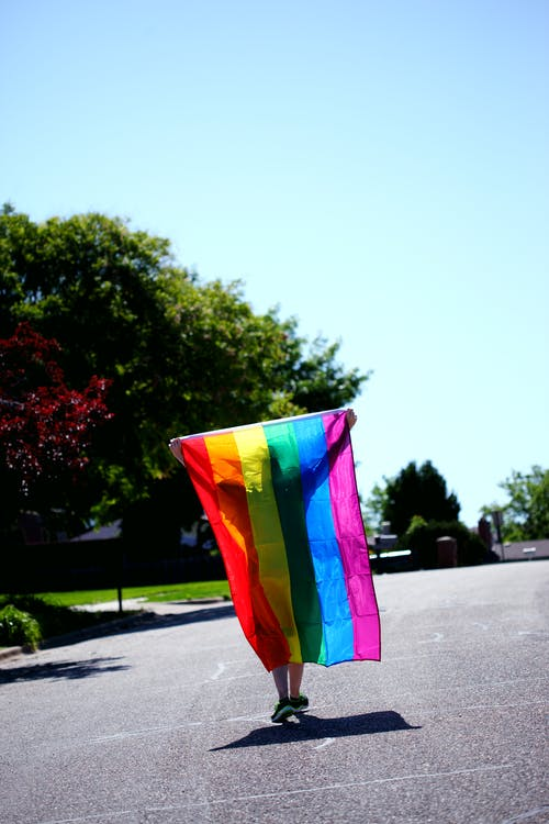 Person Walking while Holding Rainbow Colored Flag