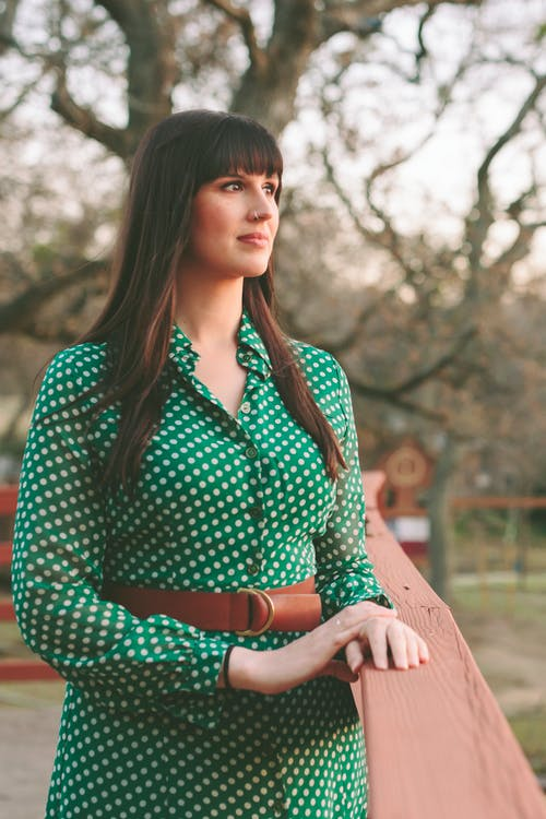 Selective Focus Photo of Woman in Green and White Polka-dot Long-sleeved Dress Standing Near Wooden Railing Looking into the Distance