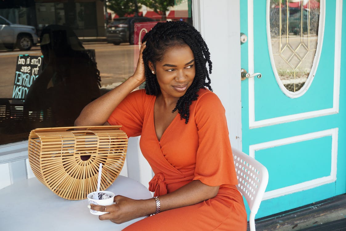 Photo of Smiling Woman in Orange V-neck Short-sleeved Dress Sitting Outside Store Holding Ice Cream While Looking Away