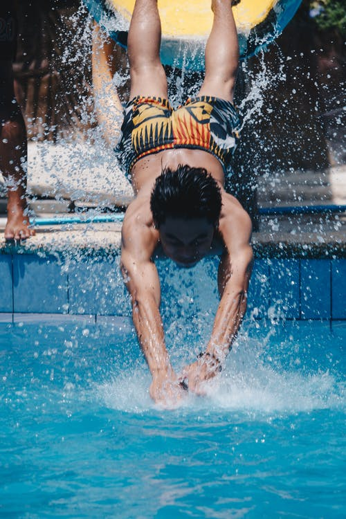 Man Jumping Towards Pool