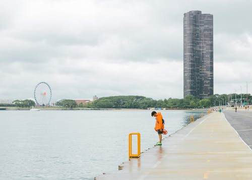 Photo of a Man Standing in Front of Body of Water