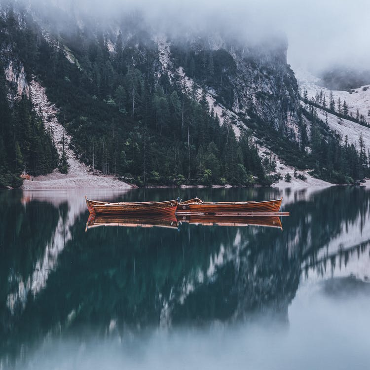 Boats at Calm Body of Water by Mountain Slip
