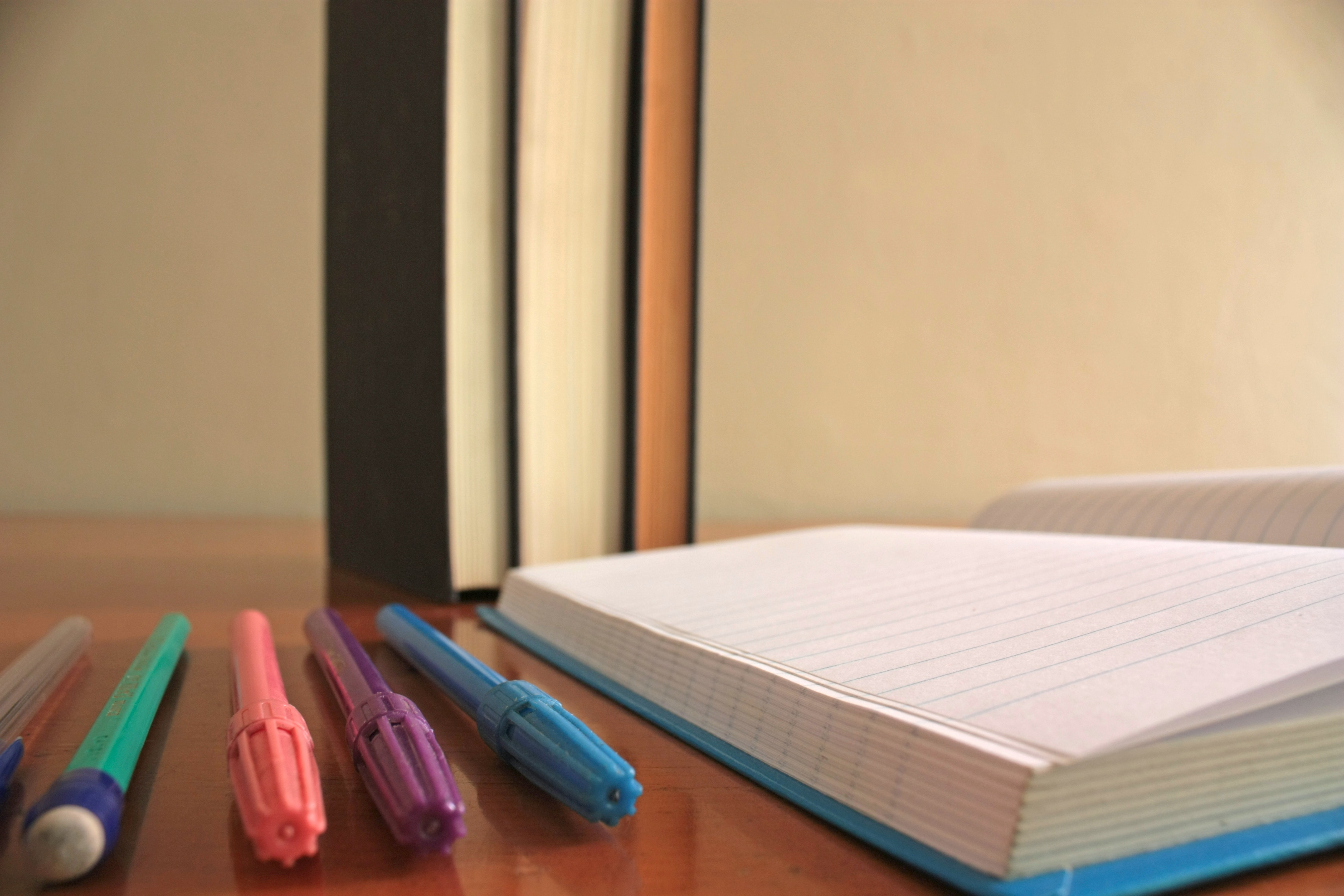 Five Assorted-color Pens Beside Blue Lined Paper