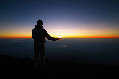 Photo of Person Standing On Top of Mountain