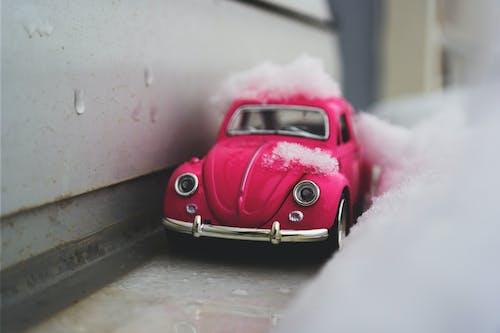 Red Volkswagen Beetle Die-cast Metal Model Beside White Wall