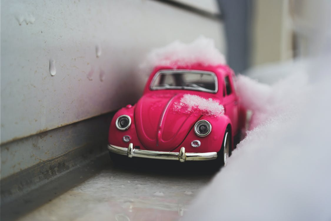 Red Volkswagen Beetle Die-cast Metal Model Beside White Wall