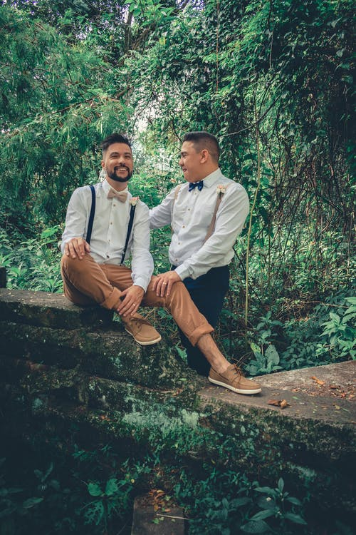 Two Man Sitting and Standing Outdoors