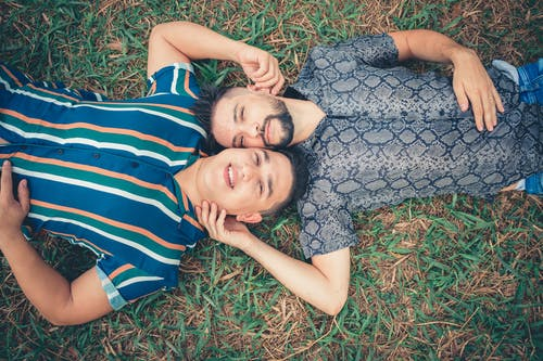 Two Men Lying on Green Grass