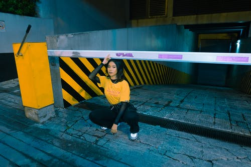 Photo of Woman in Yellow T-shirt and Black Pants Squat Posing Near Barrier Gate