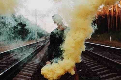 Photo of Man Standing Between Train Track Holding Yellow Smoke Bomb