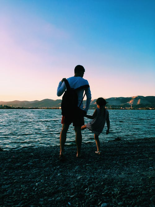 Man And Child Standing On Shore