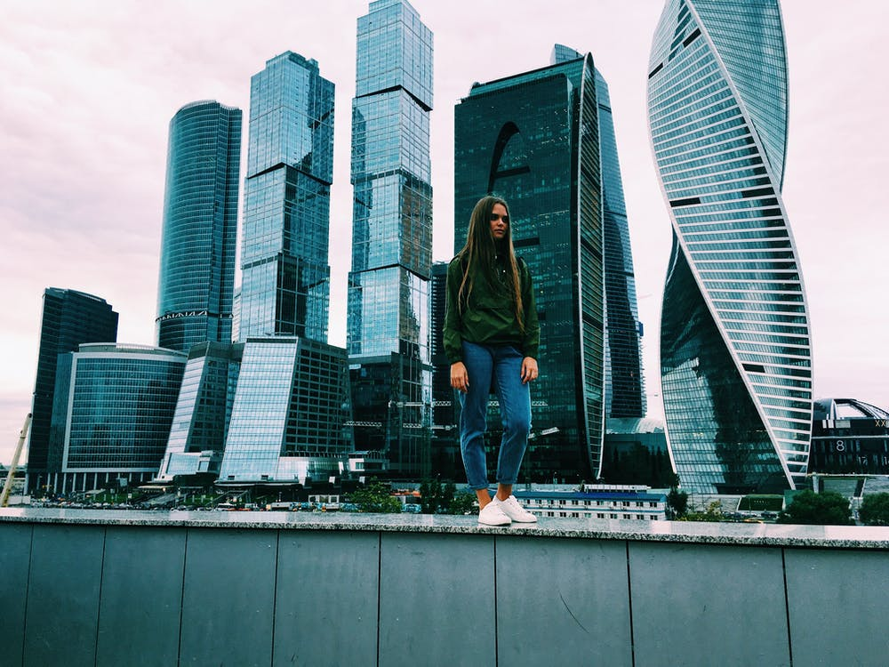 Photo of a Woman Standing in Front of Buildings