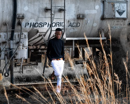 Photo of Man Standing Beside Grey Tank Car Posing