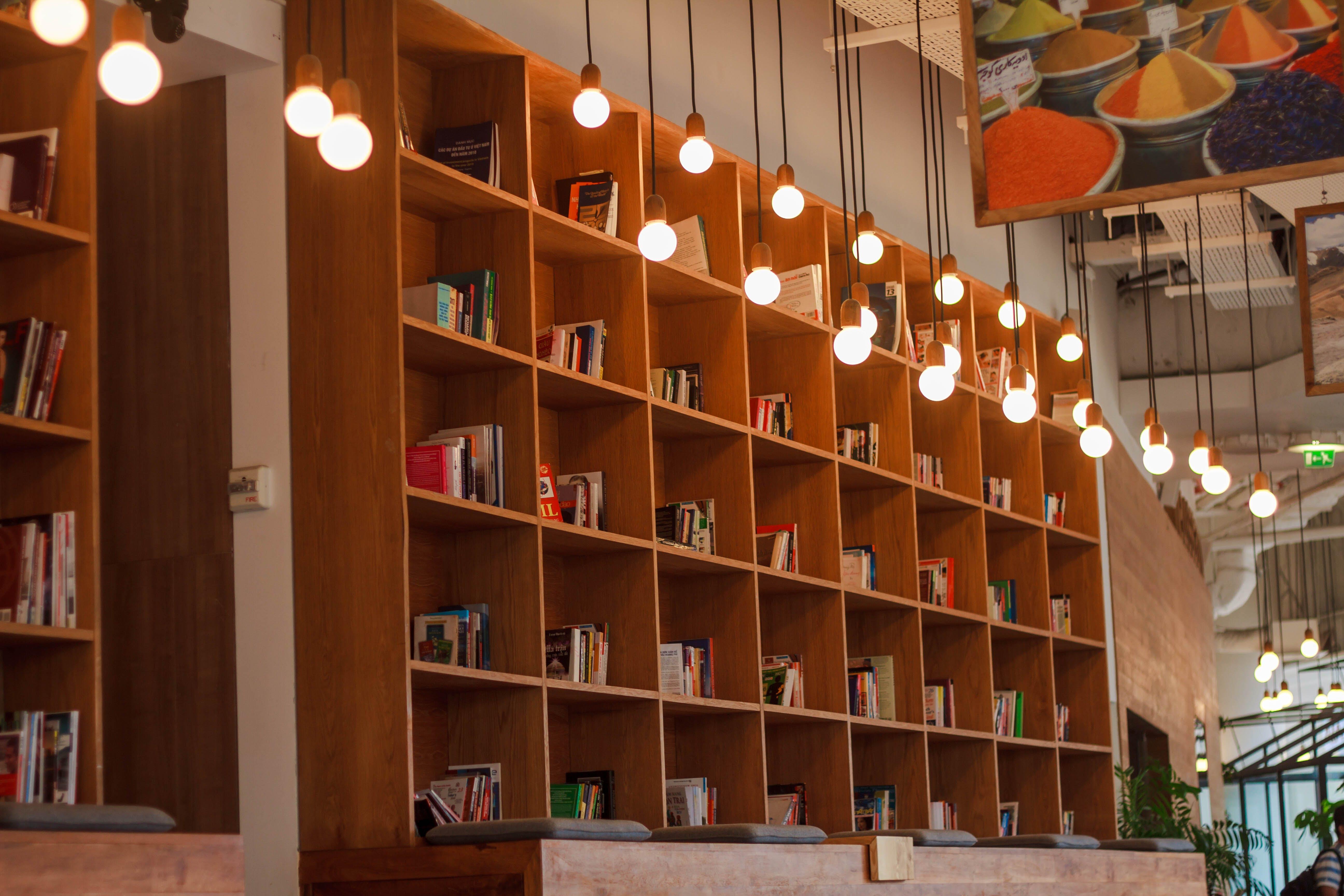 Books Inside Bookshelf Near Lit Pendant Lights