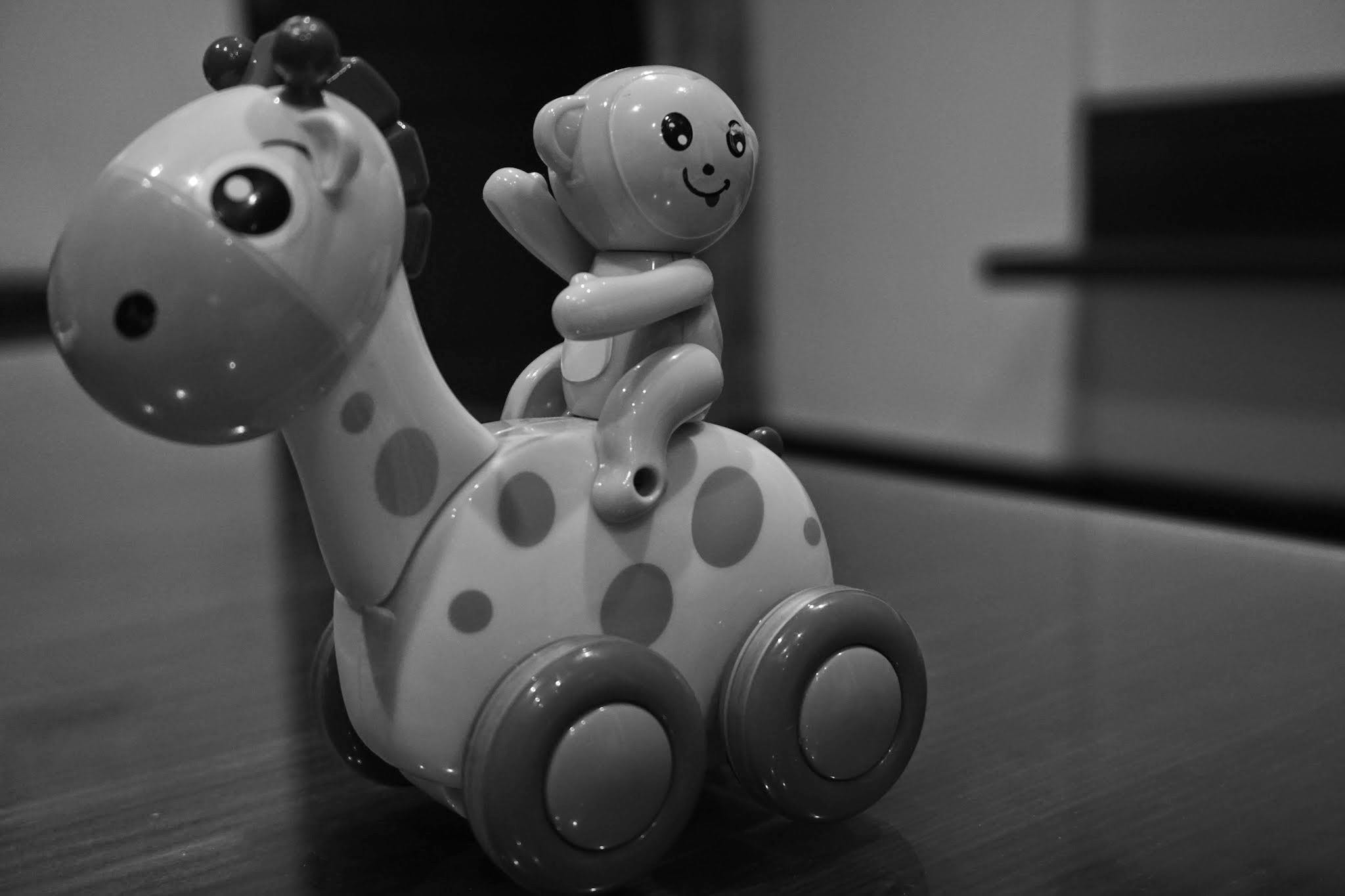 Grayscale Photo of Giraffe and Monkey Plastic Toy on Floor
