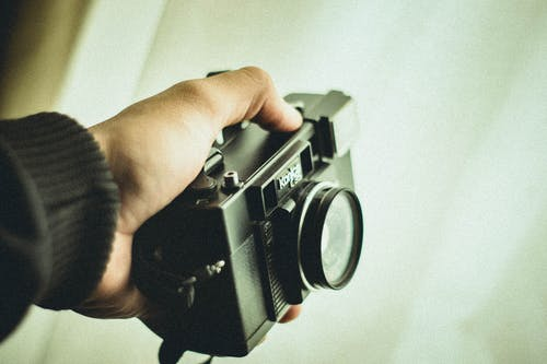 Close-up Photo of Person's Hand Holding Black Konica C35 Camera
