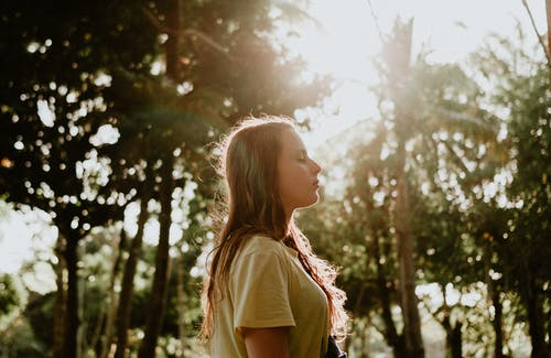 Side View Portrait Photo of Woman in Yellow T-shirt Standing With Her Eyes Closed With Trees in the Background