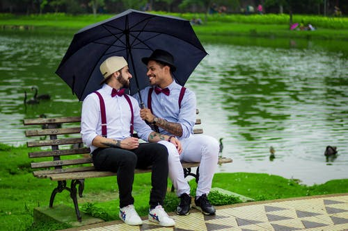 Two Man With Umbrella Sitting on Bench