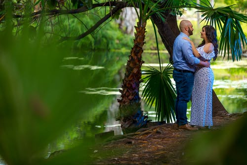 Man And Woman Standing Beside Green Palm Tree