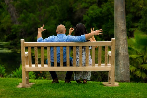 Back View Photo of Couple Sitting on Brown Wooden Bench Holding Out Their Hands Spelling The Word Love With Their Fingers