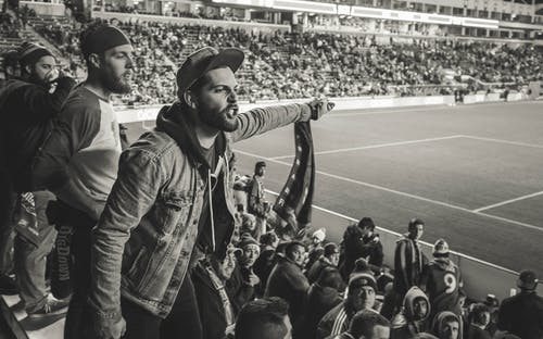 Monochrome Photo of Man Wearing Jacket Pointing Finger at Stadium