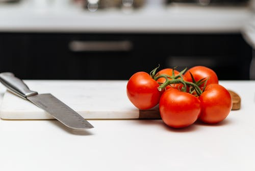 Five Tomatoes on Chopping Board